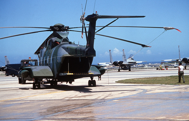 A left rear view of an HH-3E helicopter assigned to the 33rd Aerospace Rescue and Recovery Squadron. Visible in the background is an F-15 Eagle aircraft parked on the flight line