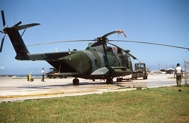 A right rear view of an HH-3E helicopter assigned to the 33rd Aerospace Rescue and Recovery Squadron. Visible in the background is an F-15 Eagle aircraft parked on the flight line