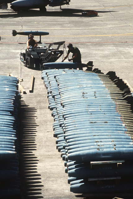 Ground crewmen use a bomb loader to pick up a Mark 82 500-pound practice bomb during operations on the flight line for Exercise COPE THUNDER 83-7
