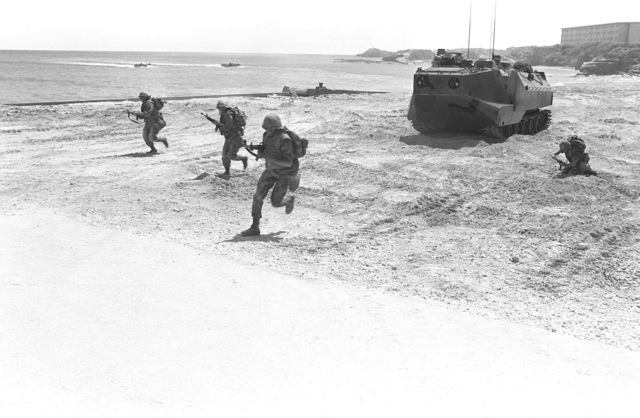 Marines conduct a mock beach assault from an LVTP-7 (tracked landing vehicle, personnel) during a training exercise. Two other LVTPs are approaching the beach in the background