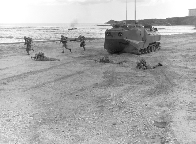 Marines conduct a mock beach assault from an LVTP-7 (tracked landing vehicle, personnel) during a training exercise. Another LVTP-7 is approaching the beach in the background