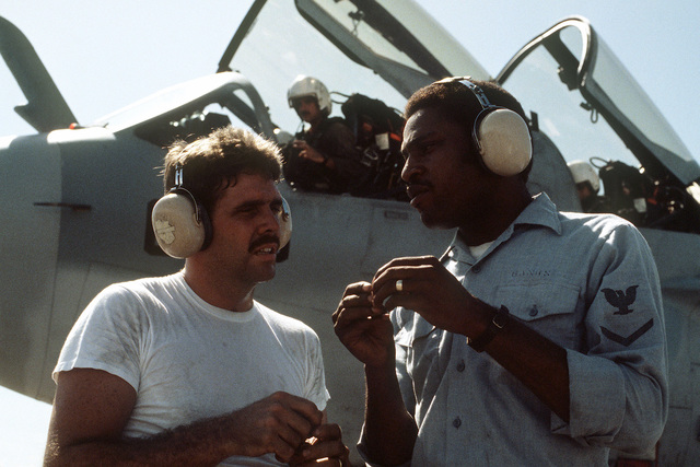 Navy ground crewmen discuss flight operations on the flight line during Exercise COPE THUNDER 83-7. A Navy pilot from Tactical Electronic Warfare Squadron 136 (VAQ-136) sits in the cockpit of an EA-6B Prowler aircraft in the background