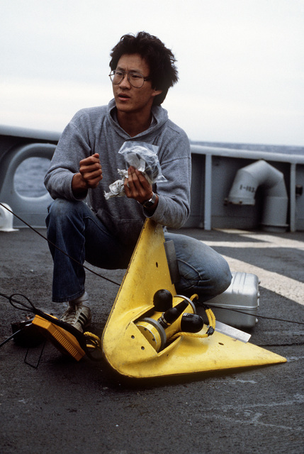 A technician services a sonar device aboard a ship involved in salvage operations for downed Korean Air Lines Flight 007 (KAL-007).  The commercial jet was shot down by Soviet aircraft over Sakhalin Island on August 30, 1983 in the Sea of Japan.  All 269 passengers and crewmen were killed