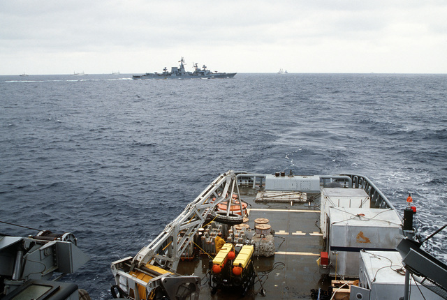 Close-up view of the stern section of the fleet tug USNS NARRAGANSETT (T-ATF 167) with a sonar device visible on deck.  The Soviet guided missile cruiser PETROPAVLOVSK (565), on the horizon, is shadowing salvage operations for downed Korean Air Lines Flight 007 (KAL-007) in which the tug is taking part.  The commercial jet was shot down by Soviet aircraft over Sakhalin Island on August 30, 1983 in the Sea of Japan.  All 269 passengers and crewmen were killed