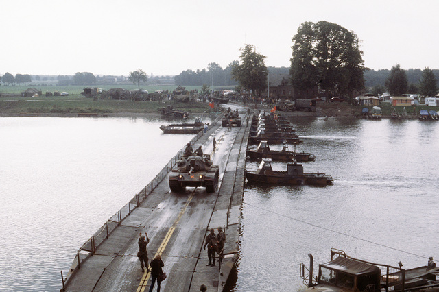 US 1ST Cavalry Division M60 main battle tanks cross a ribbon bridge spanning the Maas River during REFORGER/AUTUMN FORGE '83. Combat support boats are used to hold the bridge in place