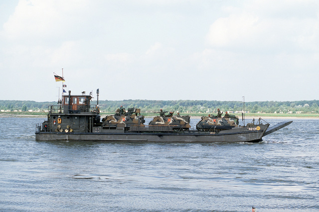 A Federal German Army landing craft ferries US 1ST Cavalry Division armored personnel carriers across the Rhine River near Wesel during REFORGER/AUTUMN FORGE '83 exercise. The APC towards the stern of the landing craft is an M901 Improved TOW Vehicle and the others are M113s