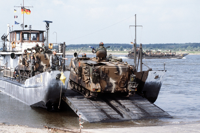 U.S. 1ST Cavalry Division M-113 armored personnel carriers are loaded aboard a Federal German Army landing craft for transport across the Rhine River during Reforger/Autumn Forge '83