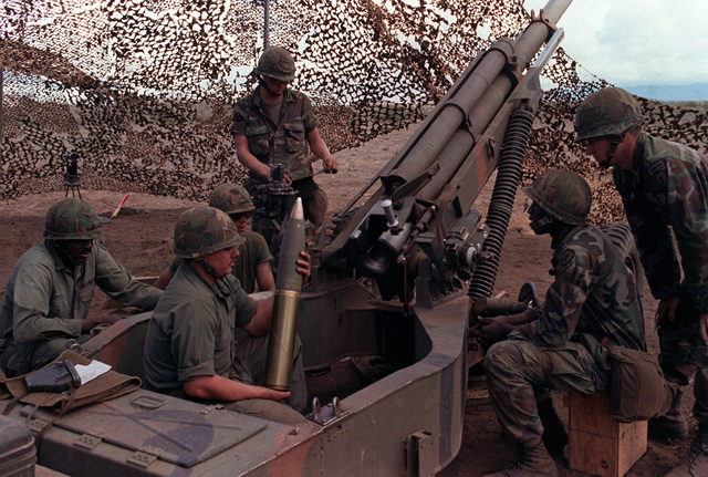 Private First Class Dale Warner, Number 1 man, Battery B, 13th Field Artillery, 25th Infantry Division, prepares to load a round into an M-102 105 mm howitzer during a live-fire artillery exercise the US Army's Pohakuloa Training Area