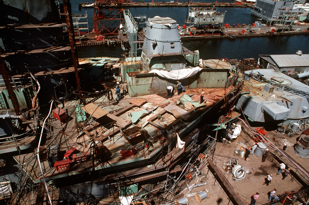 A port amidships view of the battleship USS IOWA (BB 61) during its reactivation at Ingalls Shipbuilding Corp. The structure in the center is the main battery director barbette. To port is the replenishment-at-sea outrigger, and to starboard, the aft 16-inch/50-caliber gun turret