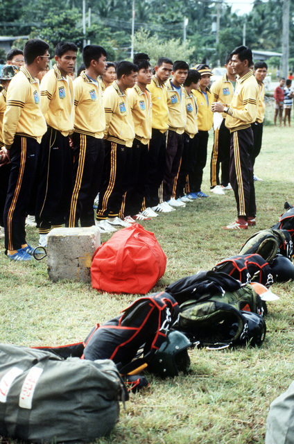 A Thai jumpmaster gives final instructions to his parachute team as they prepare for a jump during Operation MITRAPAB (Thai word for friendship), an annual parachute demonstration conducted by the Thai military and the Joint United States Military Advisory Group (JUSMAG). Proceeds from the event are used to build schools in Thailand