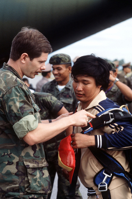 An American serviceman helps a Thai parachutist with his gear prior to a jump during Operation MITRAPAB (Thai word for friendship), an annual parachute demonstration conducted by the Thai military and the Joint United States Military Advisory Group (JUSMAG). Proceeds from the event are used to build schools in Thailand