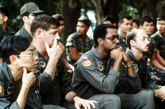 United States Air Force personnel listen to a lecture on identification of edible plants given by members of the Royal Thai Army Special Forces during jungle survival cross-training