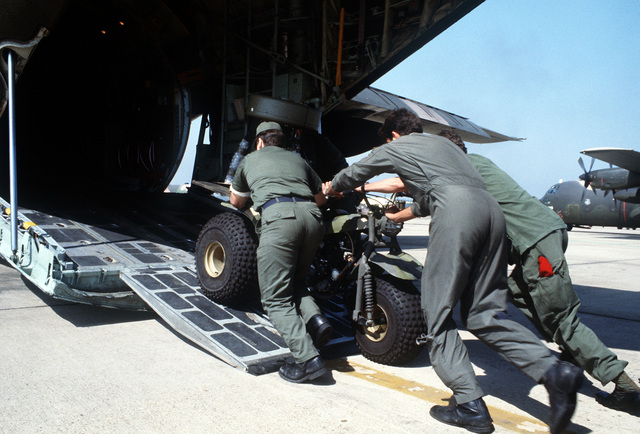 Air Force personnel push a three-wheeled all-terrain vehicle into the cargo hold of a C-130 Hercules aircraft for transport to Travis Field, Georgia, during the 314th Tactical Airlift Wing's operational readiness exercise Purple Penny