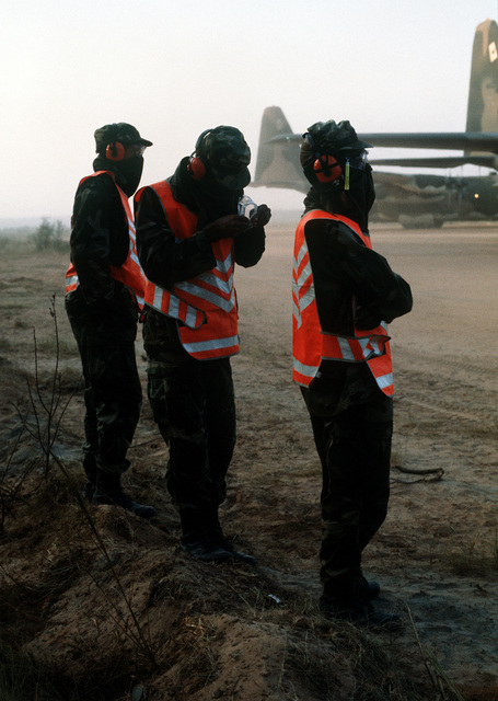 Crew chiefs, wearing camouflaged protective clothing, prepare to marshal aircraft and cargo to predetermined parking areas at the Remagen Drop Zone airfield, approximately 40 miles from Travis Field. They are participating in the 314th Tactical Airlift Wing`s operational readiness exercise Purple Penny