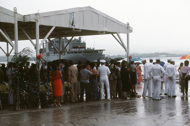 Families of the crew aboard the combat stores ship USS NIAGARA FALLS (AFS 3) stay dry under a pivilion at Naval Station Guam while welcoming the ship (background) into port
