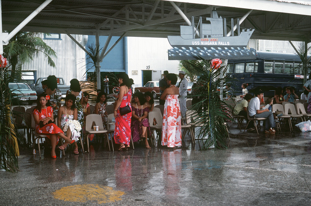 Family and friends of the crewmen aboard the combat stores ship USS NIAGARA FALLS (AFS 3) wait under a pavilion at Naval Station Guam for the ship to dock