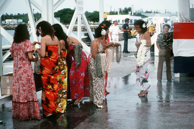 Guamanian women wait at Naval Station Guam to welcome the crew of the combat stores ship USS NIAGARA FALLS (AFS 3) into port