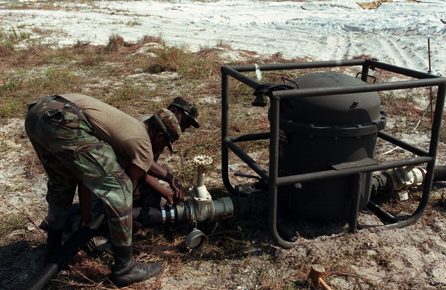 Members of the 549th Engineer Company attach a fuel hose to a fuel filter of a temporary petroleum terminal being built for exercise Bold Eagle '84