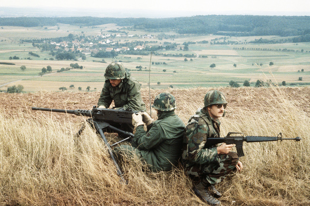 SENIOR AIRMAN (SRA) Lewis Qualkin and AIRMAN First Class (A1C) Jayme Tavernier from the 3700th Security Police Squadron, man a .50-cal. Browning machine gun as SRA Charlie Costello from the 375th SPS provides rear defense with an M16 rifle during Exercise REFORGER '83