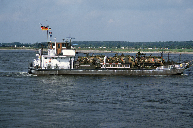 Starboard beam view of a West German Army utility landing craft transporting US soldiers and M113 armored personnel carriers across the Rhine River during Exercise REFORGER '83