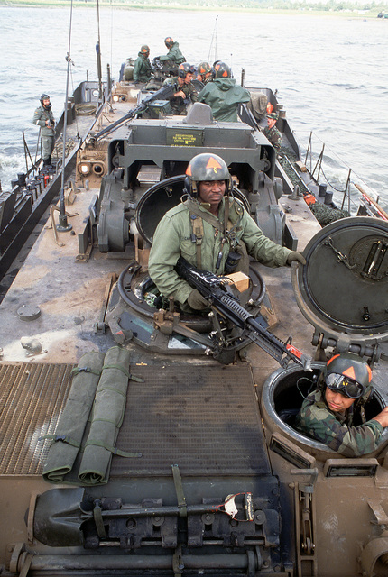 US soldiers, aboard an M113 armored personnel carrier, cross the Rhine River in a West German landing craft during Exercise REFORGER '83