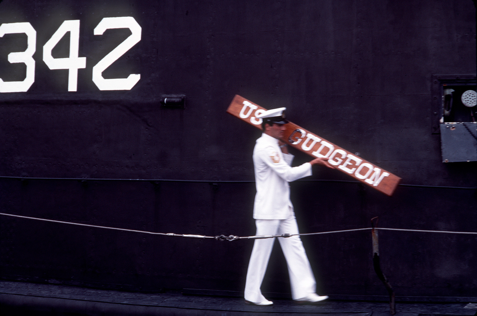 A Turkish sailor removes the name from the Tang class submarine ex-USS GUDGEON (SSAG 567) during the transfer ceremony. The GUDGEON was decommissioned and is being immediately transferred to the Turkish Navy on a five-year lease. The submarine is being renamed to TCG HIZIR REIS (S 342)