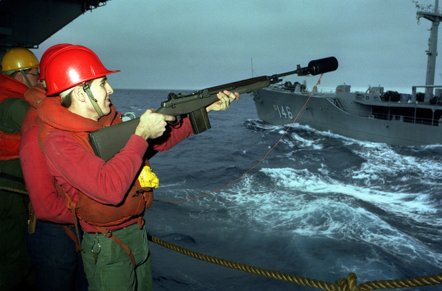 A crewmember aboard the aircraft carrier USS KITTY HAWK (CV 63) fires an M14 rifle equipped with a line throwing device for use during underway replenishment operations with the Neosho class oiler USNS KAWISHIWI (TAO 146), seen in the background