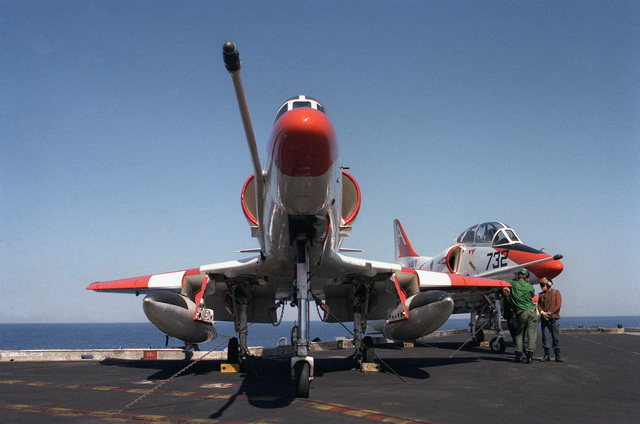 A left side view of two F/A-18 Hornet aircraft on the flight deck of the aircraft carrier USS KITTY HAWK (CV 63). The aircraft are assigned to strike Fighter Squadron 125 (VFA-125)