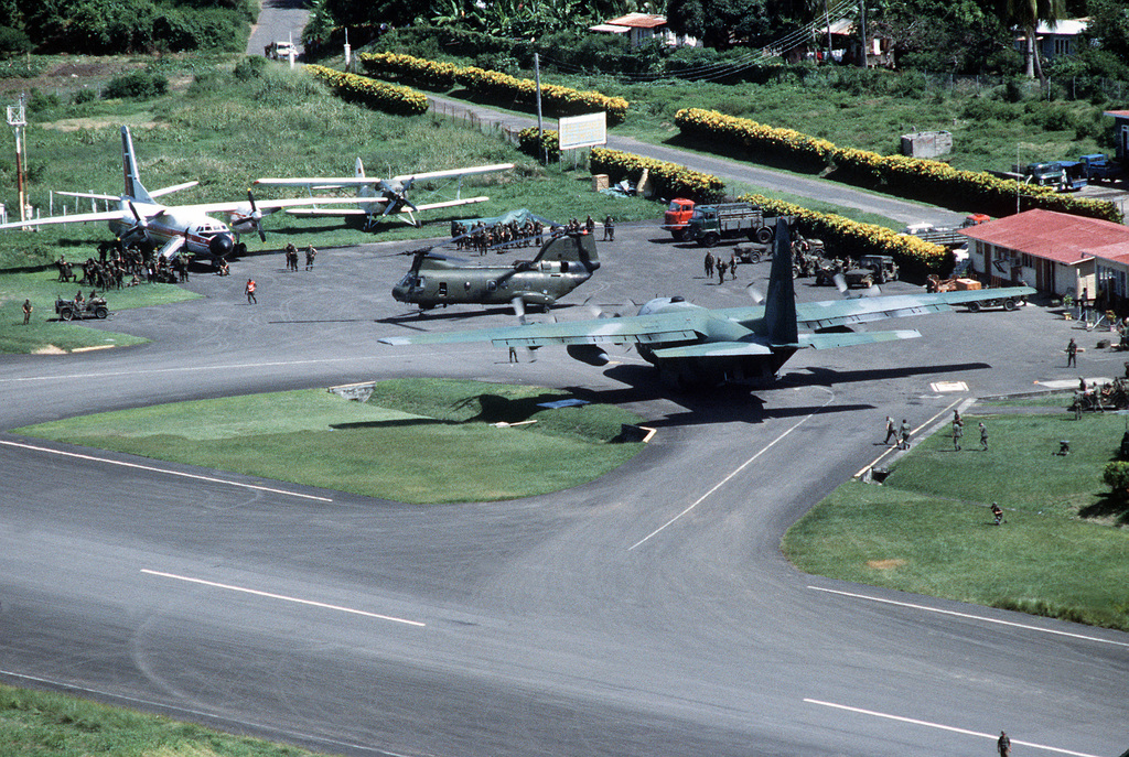 An elevated view of Pearls Airport with a C-130 Hercules aircraft and a CH-46E Sea Knight helicopter on the flight line during Operation Urgent Fury. A Soviet-made AN-26 Curl transport of Cubana airlines, left background, and a Soviet AN-2 Colt aircraft, right background, were seized during the operation