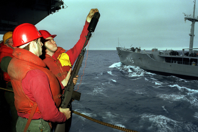 Crewmembers aboard the aircraft carrier USS KITTY HAWK (CV 63) prepare an M14 rifle equipped with a line throwing device for use during underway replenishment operations with the Neosho class oiler USNS KAWISHIWI (TAO 146), seen in the background