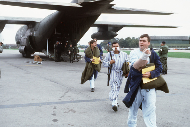 Members of the 1ST Squadron, 3rd Armored Cavalry Regiment, exit from a C-130 Hercules aircraft after a flight from Ramstein Air Base, West Germany. They are acting as patients during a reserve medical evacuation exercise conducted by the 146th Aeromedical Evacuation Squadron
