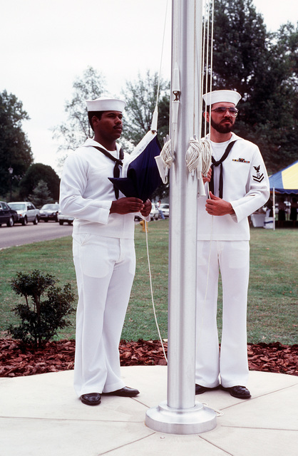 Two sailors prepare to raise the U.S. Naval Space Command flag during the unit's commissioning ceremony