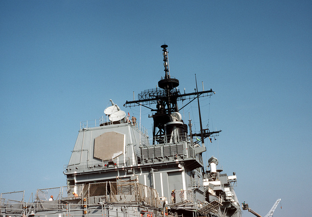 A view of the superstructure of the guided missile cruiser USS TICONDEROGA (CG-47) as seen from the ship's aft. The large block-like structure to the left houses the SPY-1A radar antenna. Atop the structure are two Mark 99 missile directors. To the right of it is a satellite receiving antenna. On the mast is an SPS-49 radar antenna