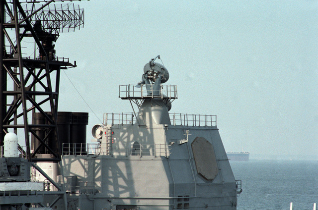 An elevated view of the aft array of radar equipment aboard the Ticonderoga class Aegis guided missile cruiser USS TICONDEROGA (CG 47) moored at the naval station. Note the SPS-49 three-dimensional air search radar on the platform of the main mast, left, the SPY-1A radar, right, and the Mark 99 missile directors, top right.