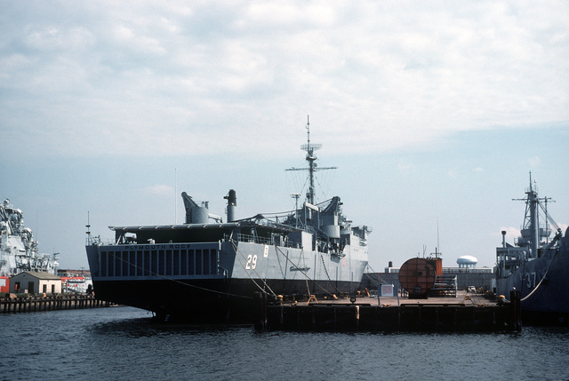 A starboard quarter view of the dock landing ship PLYMOUTH ROCK (LSD 29) moored at the Navy's deactivated ships pier, located across from the Norfolk Naval Shipyard on the James River. The PLYMOUTH ROCK was towed here from Little Creek, Virginia, after decommissioning on September 29, 1983