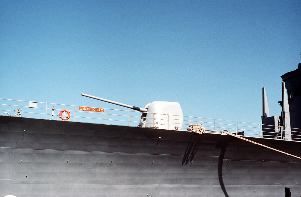 A view of the forward Mark 45 5-inch DP gun on the guided missile destroyer USS KIDD (DDG-993). Behind the gun are the upright arms of the Mark 26 missile launcher