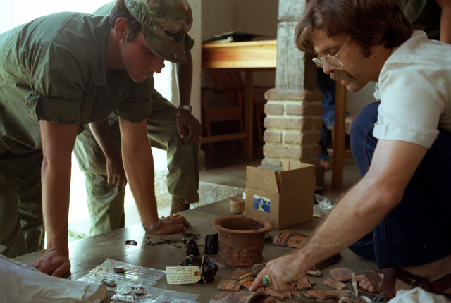 Dr. Kenneth Hirth, Department of Anthropology, University of Kentucky, looks at some of the artifacts that the 360th Transportation Company helped him to move during the Ahuas Tara II (Big Pine) operation