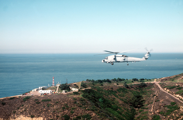 Air-to-air left side view of a Navy SH-60B Seahawk helicopter from Light Helicopter Anti-Submarine Squadron 41. The helicopter is about to fly over the Point Loma Lighthouse