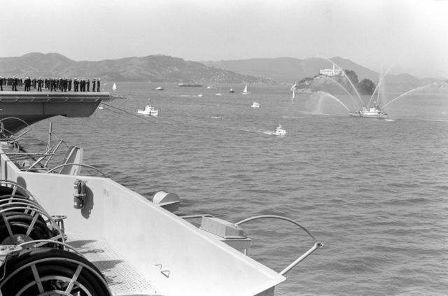 Crewmen stand on the flight deck of the nuclear-powered aircraft carrier USS ENTERPRISE (CVN 65) as it passes Alcatraz Island. A harbor tug sprays water into the air to welcome the carrier back from its deployment