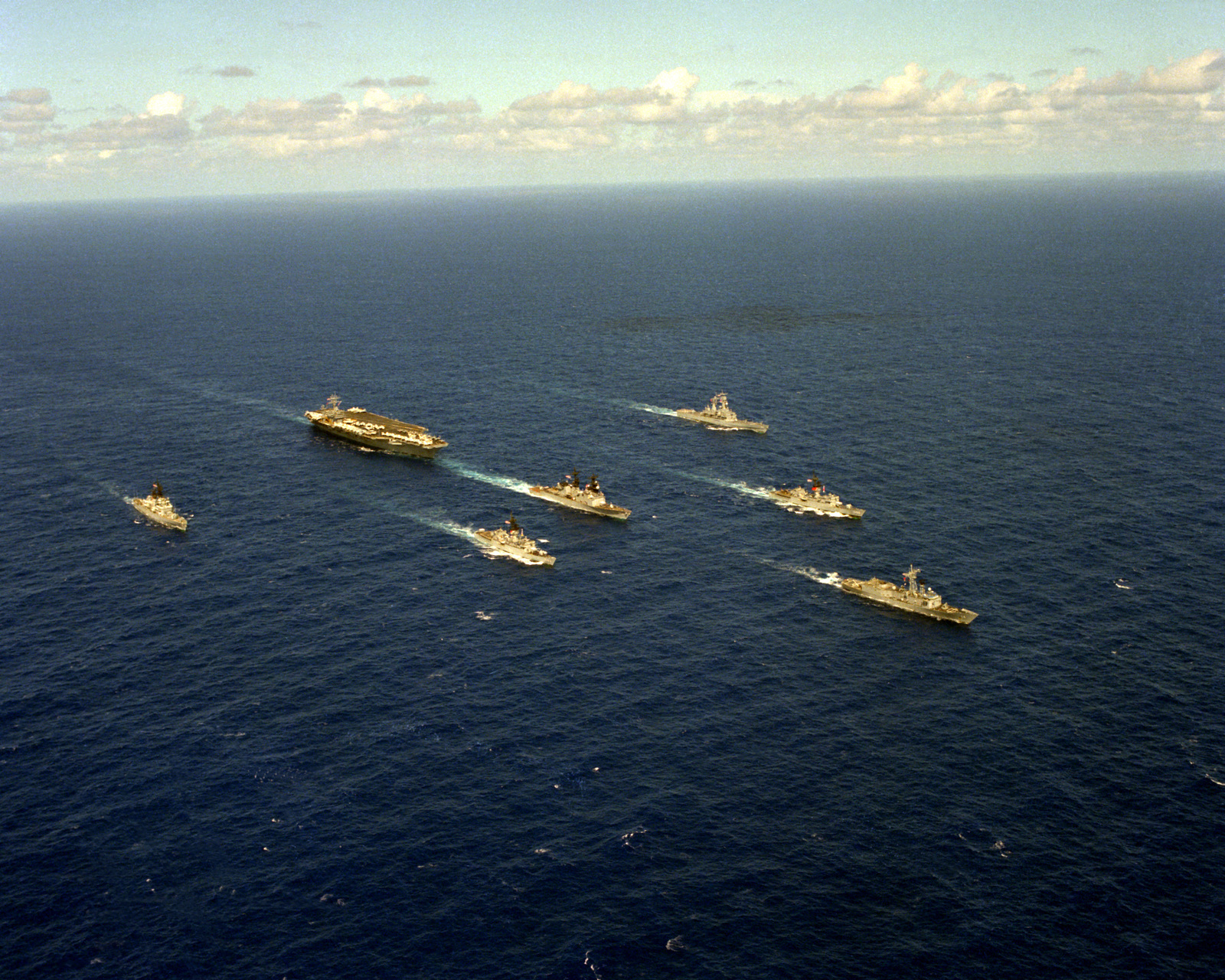 A starboard bow view of the nuclear-powered aircraft carrier USS CARL VINSON (CVN-70) underway near Hawaii with its battle group. Left to right: the guided missile cruiser USS WORDEN (CG-18), the frigate USS COOK (FF-1083), the destroyer USS HEWITT (DD-966), the nuclear-powered guided missile cruiser USS TEXAS (CGN-39), the frigate USS BARBEY (FF-1088) and the guided missile frigate USS SIDES (FFG-14)