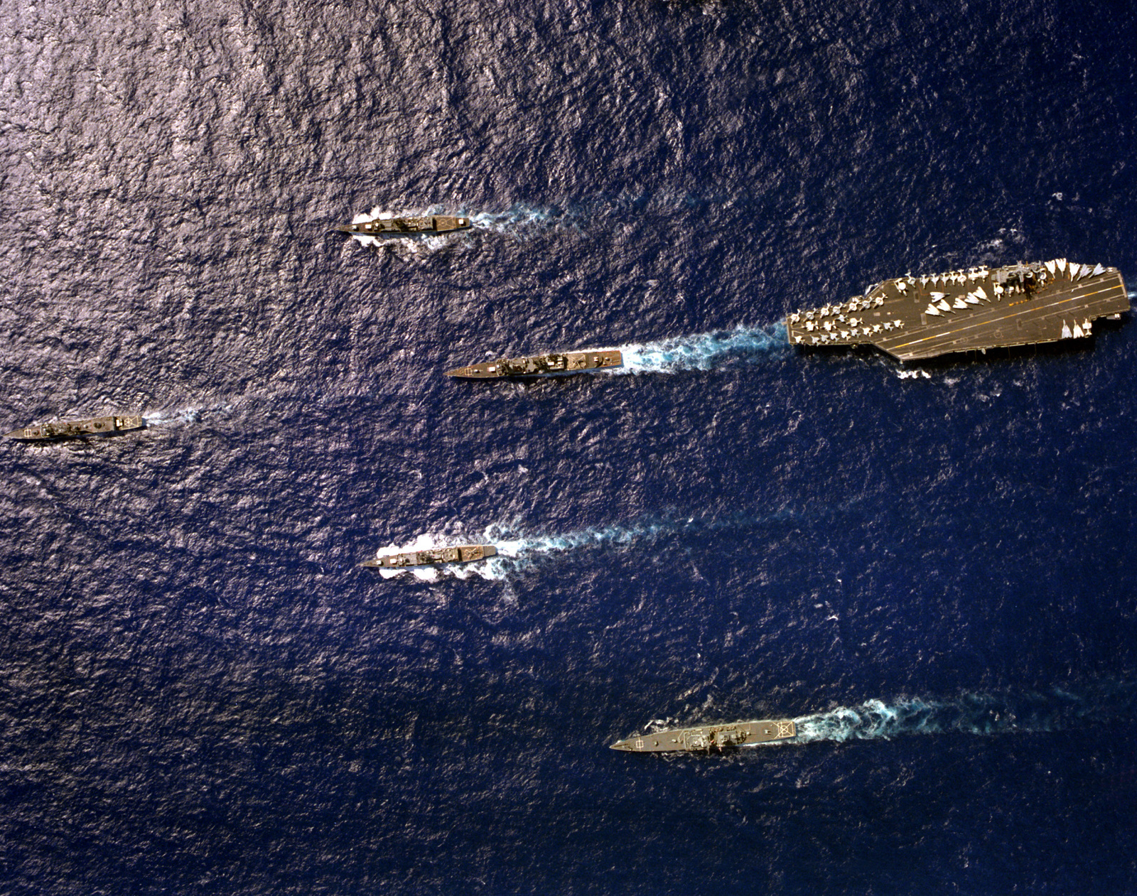 An overhead view of the nuclear-powered aircraft carrier USS CARL VINSON (CVN-70) underway near Hawaii with its battle group. Top to bottom are the frigate USS COOK (FF-1083), the destroyer USS HEWITT (DD-966), the frigate USS BARBEY (FF-1088), the nuclear-powered guided missile cruiser USS TEXAS (CGN-39) and, leading the formation, the guided missile frigate USS SIDES (FFG-14)