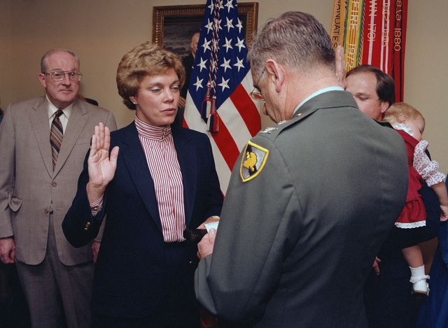 Colonel (COL) Robert W. Berry, professor of law at the US Military Academy, West Point, New York,  administers the oath of office to Susan J. Crawford, newly appointed general counsel to the Department of the Army.  Undersecretary of the Army James R. Ambrose is in the left rear of the picture