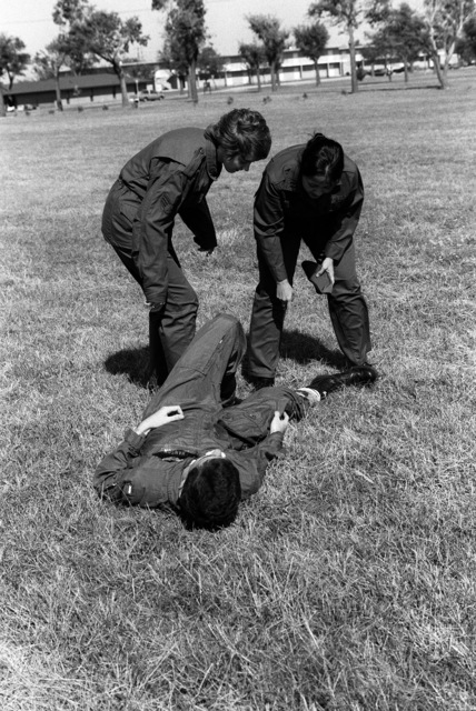 """Captain (Dr.) April McVey, right, CHIEF of Aeromedical Services for the US Air Force Clinic, evaluates an """"injury"""" during a battlefield triage exercise for mini-medical Red Flag training"""
