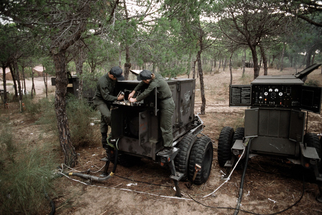 Two power production specialists perform maintenance on a mobile power generator during the joint US/Spanish military Exercise CRISEX 83