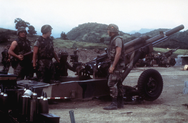 82nd Airborne Division artillerymen prepare to load a round into their M102 105 mm howitzer during a fire mission in support of Operation URGENT FURY