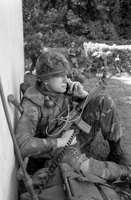 A Marine checks in with his command post via field radio during Operation URGENT FURY. He is armed with an M16A1 rifle