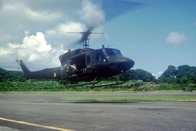 A Marine Corps UH-1N Iroquois helicopter prepares to touch down during Operation URGENT FURY. The helicopter is equipped with a door-mounted M60D machine gun
