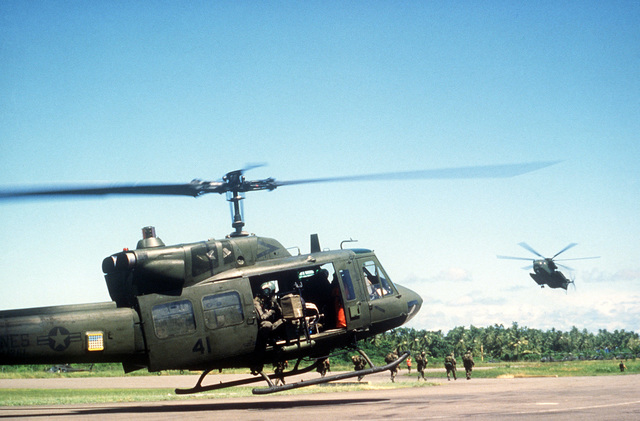 A Marine Corps UH-1N Iroquois helicopter touches down during Operation URGENT FURY. The helicopter is equipped with a door-mounted M60D machine gun. A CH-53 Sea Stallion helicopter approaches in the background