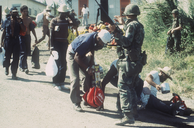 A member of the 16th Military Police Brigade, XVIII Airborne Corps, stops a group of Cuban prisoners while manning a checkpoint