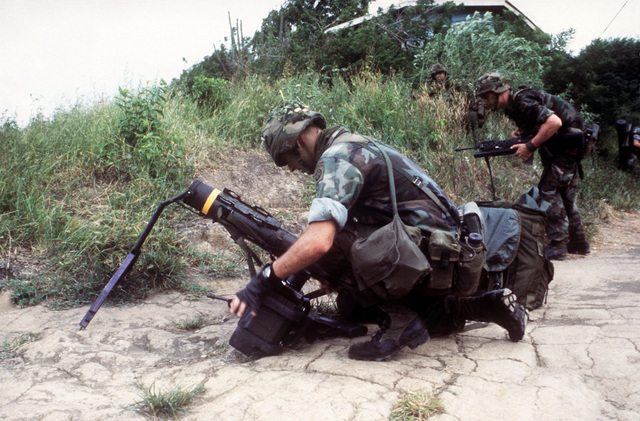A member of the 82nd Airborne Division prepares to attach the tracker assembly to the launch tube of an M47 Dragon anti-tank weapon during Operation URGENT FURY. The soldier on the right has an M203 40 mm grenade launcher attached to his M16A1 rifle